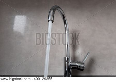 Horizontal view of the silver faucet in the bathroom. Water is flowing from the open tap. Interior of a modern bathroom with fittings.