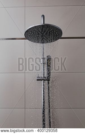 Shower with a tiled background in the bathroom. Water flies from chrome showers in drops. Bathroom fittings as an element of equipment and a modern design at home.