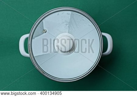 One White  Enameled Pan Covered With A Glass Lid Stands On A Green Table