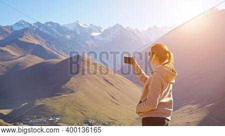 Amazed Woman Wearing Hoodie And Sunglasses Makes Video Of Breathtaking Panorama Of Beautiful Mountai