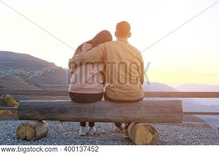 Couple Hugs Sitting On Bench On Viewing Point Against Picturesque Ancient Mountains At Sunset Backsi
