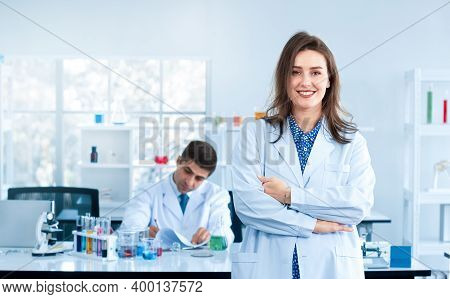 A Beautiful Young Scientist Stands Smiling In A Science Lab With A Male Scientist Sitting In The Bac