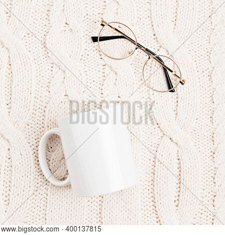 Mockup With White Mug And Glasses On White Woolen Knitted Background. Cozy Reading Concept. Flat Lay