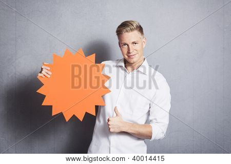 Friendly handsome man giving thumbs up while holding blank panel with space for text promoting sales isolated on grey background.