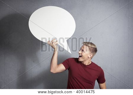 Great news: Joyful handsome man holding white blank speech bubble with space for text isolated on grey background.