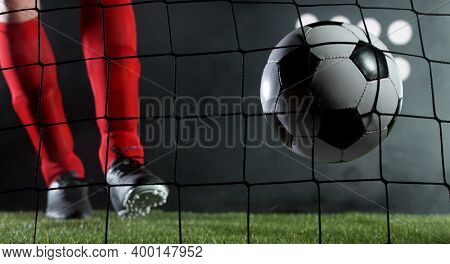 Kicking soccer ball into net, goal success concept. Isolated on black background