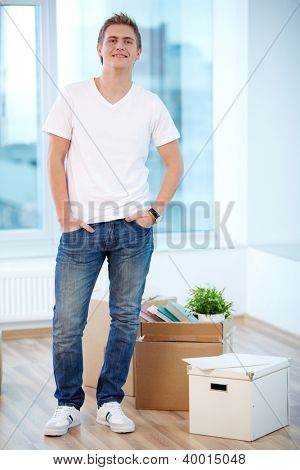 A young guy standing in new flat with boxes near by