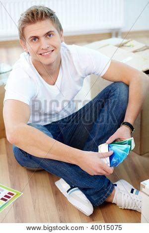 A young guy sitting on the floor of new house and choosing color from palette