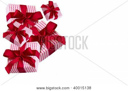 Corner of paper giftboxes with red bow on white background