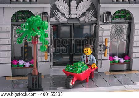 Tambov, Russian Federation - December 19, 2020 Lego Businessman Using A Wheelbarrow To Transport Mon