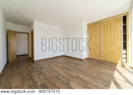 Empty Room With Dark Wooden Floating Laminate Flooring. House Interior, Wide Bedroom Or Living Room