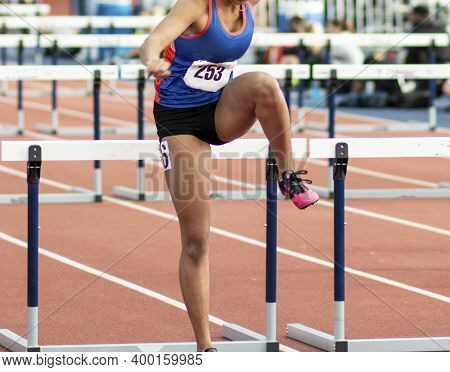 A High School Girl Racing In The Hurdles During An Indoor Competition Landing In Front Of Hurdle.