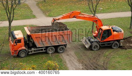 Excavator And Dump Truck. Work On The Arrangement Of Tracks