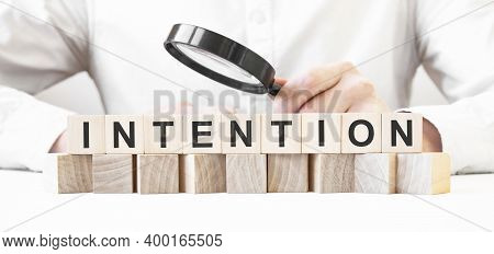 Businessman Holding Magnifier. Businessman Watch On The Wooden Cubes With Text Intention. Financial