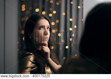 Female Party Host Looking In The Mirror Having An Idea