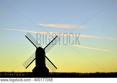 Windmill Silhouette At Dusk With Sails Against Light Blue Sky And Yellow Horizon With Wispy Clouds.