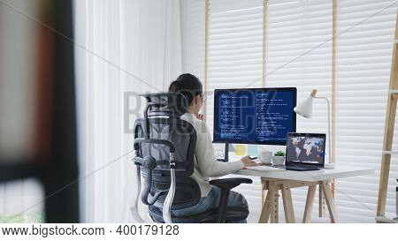 Back Rear View Of Young Asian Woman, Freelance Data Scientist Work Remotely At Home Coding Programin