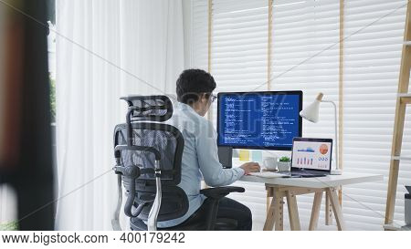 Back Rear View Of Young Asian Man, Freelance Data Scientist Work Remotely At Home Coding Programing