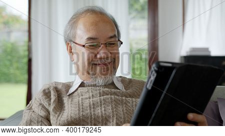 Candid Of Old Asian Retired Man Using Tablet Computer To Transfer Money Online Or Financial Payment