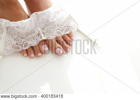 Brides Legs In A Lace Garter With A Beautiful Manicure On A White Background. High Quality Photo