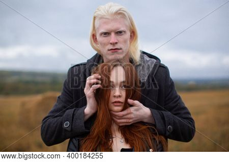 Model Shooting Of A Pair Of Unusual Appearance In A Wheat Field. Red-haired Young Woman And Albino G