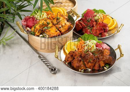 Chicken, Beef, And Pork Shashlik With Vegetable Garnish And Spicy Spices, Cooked In Tandoor. A Set O