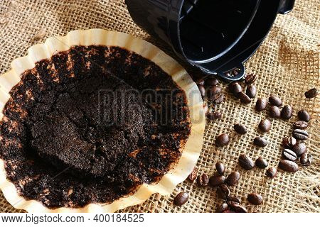An Image Of A Used Coffee Filter With Coffee Basket And Coffee Beans On Burlap.
