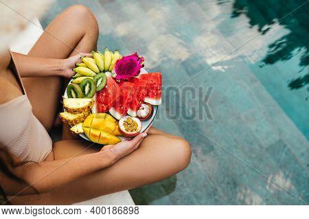 Young Unrecognizable Woman By The Pool With A Plate Of Tropical Fruits: Watermelon, Pineapple, Banan