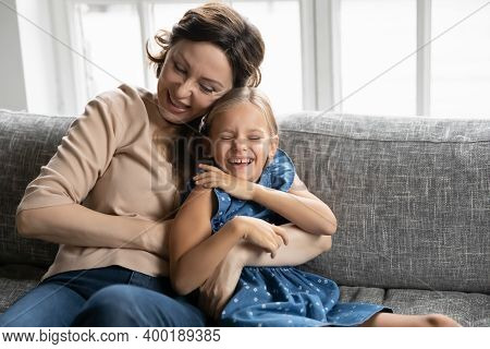 Happy Mature Grandmother And Granddaughter Having Fun, Tickling On Couch