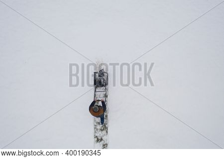 Aerial View Snowblower At Work On A Winter Day. Man Removing Snow After Blizzard Snowfall. Gardener