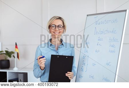 Online Schooling Concept. Portrait Of Positive German Teacher Posing Near Blackboard With Grammar Ru