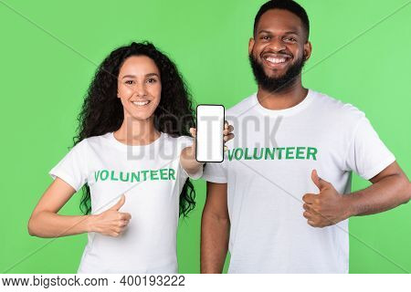Two Cheerful Volunteers Showing Phone Empty Screen Gesturing Like Approving Charity Application Stan