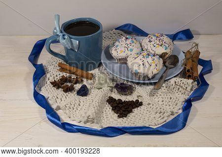 There Is A Cup Of Coffee On A White Napkin. Nearby Are Coffee Beans And A Plate Of Cakes. In Front A