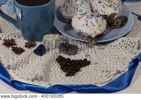 Close-up. There Is A Cup Of Coffee On A White Napkin. Nearby Are Coffee Beans And A Plate Of Cakes.