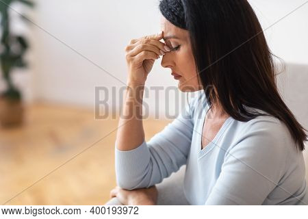 Exhaustion And Weakness. Side View Portrait Of Fatigued Upset Mature Lady Massaging Her Nose Bridge,