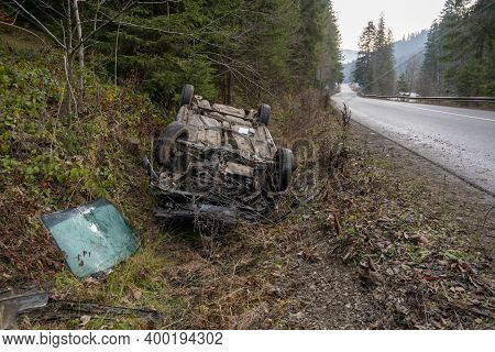The Car Got Into An Accident On The Mountain Road And Fell Upside Down. The Blue Car Turned Over In