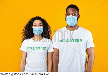 Two Diverse Volunteers Wearing Face Masks And White Uniform T-shirts Posing Standing Over Yellow Stu
