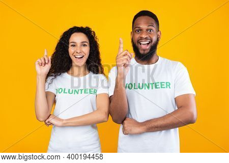 Two Diverse Volunteers Pointing Fingers Up Having Great Idea Smiling To Camera Posing Standing Over