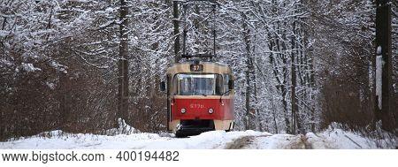 Kiev, Ukraine - December 25, 2018: Snowy Winter. Old Red Retro Tram Is Rolling (going) Along Commute