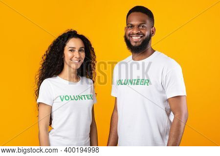 Volunteering Work. Female And Male Multiracial Volunteers Posing Smiling To Camera Wearing White Uni