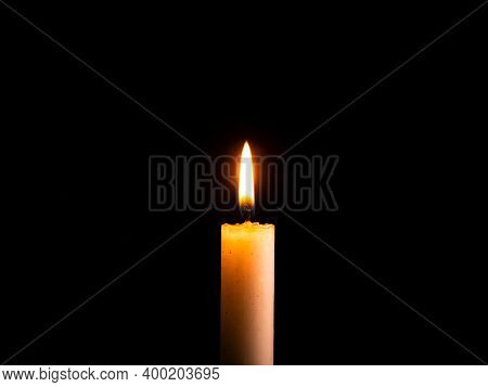 The Flame Of A Burning Wax Candle In The Dark. Flame Of Wax Candle Fire. Fire In The Dark. Day Of Re