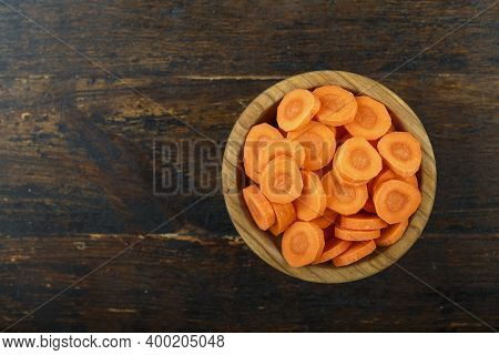 Sliced Carrots In A Bowl On A Wooden Background. Vegetable, Ingredient And Staple Food. Healthy Food