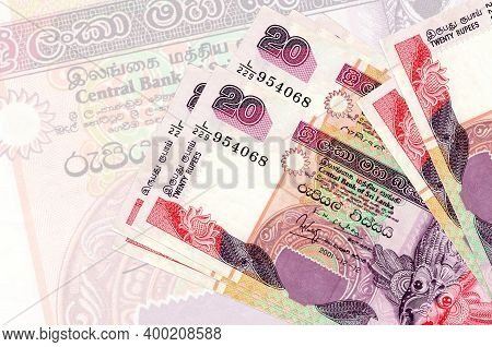 20 Sri Lankan Rupees Bills Lies In Stack On Background Of Big Semi-transparent Banknote. Abstract Pr