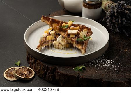 Viennese Waffles With Banana, Mango, Caramel And Mint. Classic Hot Dessert Belgian Waffles.