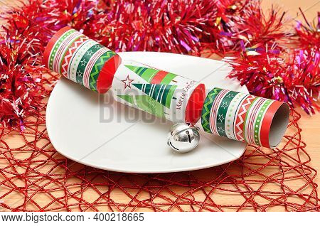 Christmas Table Decorated With A Plate, Tinsel, Bell And A Christmas Cracker