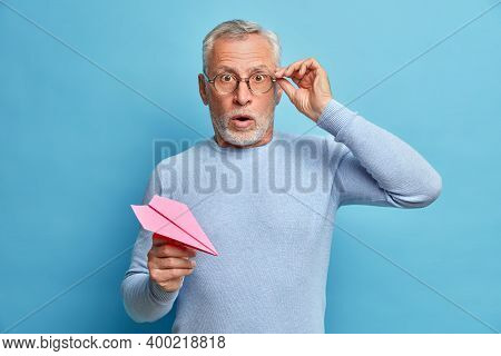Isolated Shot Of Grey Haired Man Holds Breath Keeps Hands On Spectacles Being Frightened Holds Paper