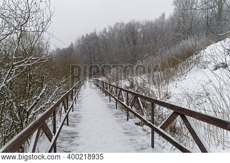 Winter Landscape With A Footbridge At The Bottom Of The Ravine.