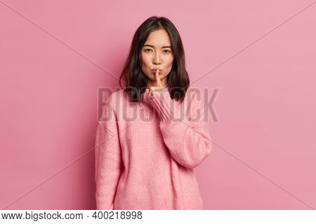 Serious Mysterious Brunette Asian Woman Presses Index Finger To Lips Makes Hush Gesture Tells Secret