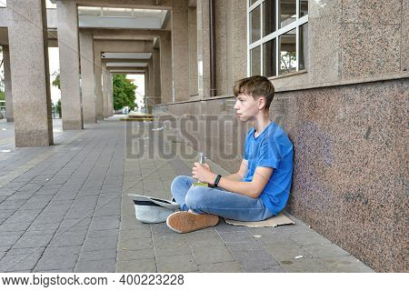 A Drunken Teenager Beggar Sits With A Drink In His Hand And Begs For Money. Teenage Alcoholism Conce