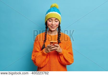 Beautiful Asian Teenage Girl With Two Combed Pigtails Types Text Messages On Modern Cellphone Wears